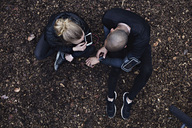 Directly above shot of couple using technologies while exercising in forest - MASF02551