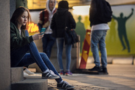Thoughtful teenager using phone while sitting on steps against friends - MASF02566