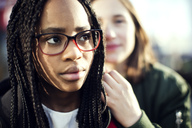 Thoughtful teenage girl wearing eyeglasses sitting with friend in city - MASF02569