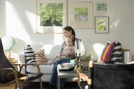 Woman sitting with baby girl on sofa at home - MASF02587