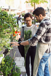 Woman buying flowers from male owner on sidewalk - MASF02590