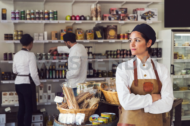 Thoughtful owner standing arms crossed while colleagues working in grocery store - MASF02593