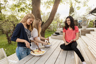 Teenage girls mixing salad at wooden table in yard - MASF02596