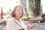 Thoughtful businesswoman looking away while listening music through smart phone on sunny day - MASF02614