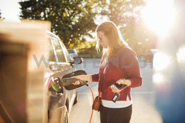 Woman holding smart phone while charging electric car at station on sunny day - MASF02632