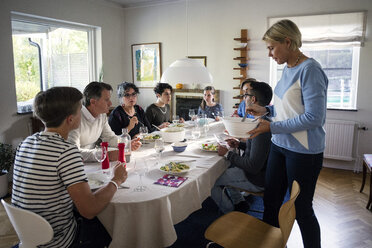 Woman serving food to family and friends at dining table in dinner party - MASF02635