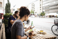 Woman having food while using mobile phone at sidewalk cafe in city - MASF02641