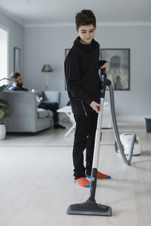 Boy cleaning floor with vacuum cleaner at home - MASF02656