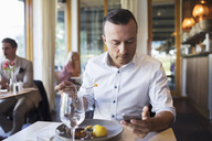 Businessman eating lunch while using mobile phone at restaurant - MASF02665