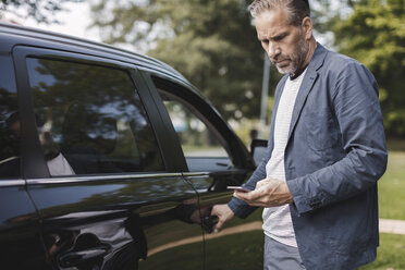 Businessman using smart phone while opening car door at park - MASF02689