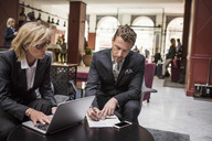 Businesswoman looking at partner signing agreement in hotel reception - MASF02701