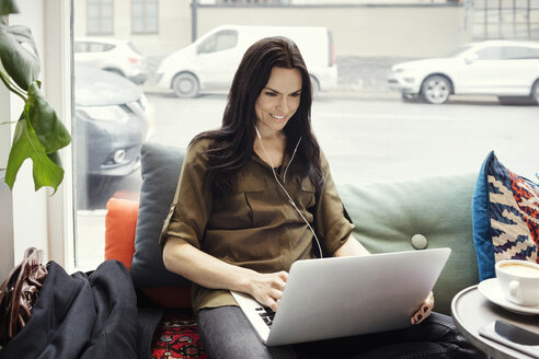 Smiling businesswoman using laptop while sitting on sofa against window - MASF02725