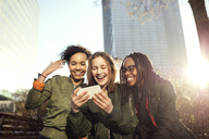 Smiling multi-ethnic friends taking selfie with smart phone in city - MASF02737