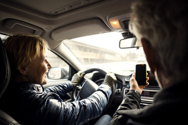 Smiling senior woman driving car while sitting by man taking selfie through smart phone - MASF02740