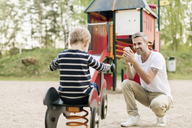 Smiling father photographing son playing on spring ride at playground - MASF02743