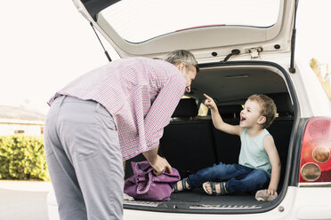 Son pointing at father while sitting in open car trunk - MASF02746