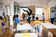 Students looking at male teacher performing handstand in classroom - MASF02752