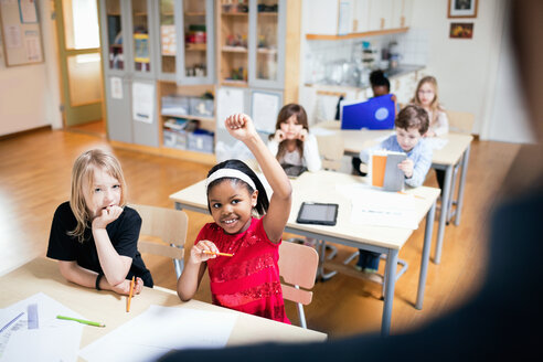 Smiling student with hand raised sitting in classroom - MASF02755