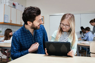Smiling teacher looking at girl holding digital tablet at desk - MASF02761
