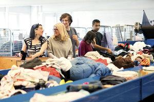 Smiling volunteers checking clothes on conveyor belt at workshop - MASF02764