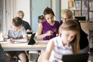 Teacher assisting schoolgirl by boy in classroom - MASF02770