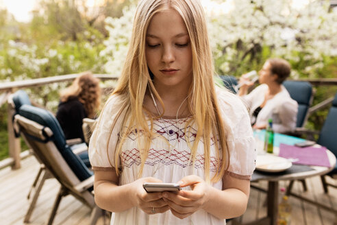 Teenage girl using smart phone at yard with family sitting in background - MASF02782