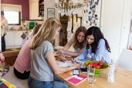 Teenage girls discussing while studying at table - MASF02791