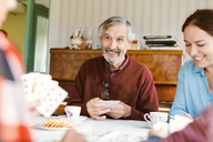 Smiling senior man playing cards with family at home - MASF02803