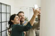 Smiling business people taking selfie while standing in office - MASF02809