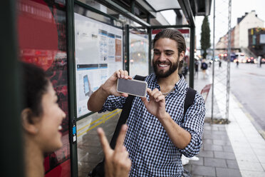Smiling man photographing female friend through smart phone at bus stop in city - MASF02821