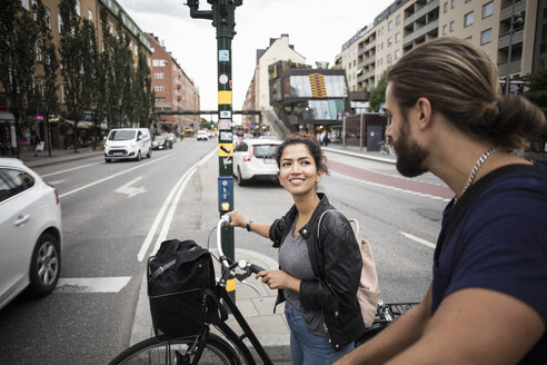 Smiling woman with bicycle looking at friend while standing amidst city street - MASF02824