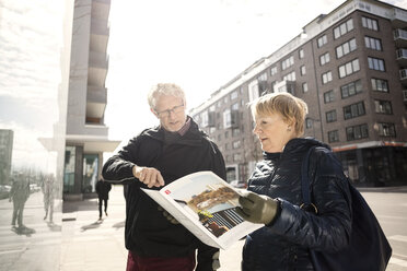 Senior couple reading catalog by building in city - MASF02842