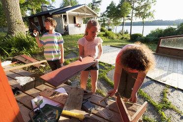 Siblings doing carpentry in yard - MASF02845
