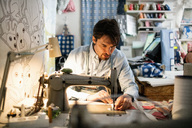Serious owner sewing fabric at shop - MASF02848