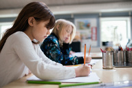 Side view of students writing on paper at desk in classroom - MASF02854