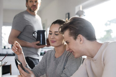 Siblings using smart phone in kitchen while father holding jug - MASF02857