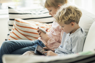 Siblings using technologies on sofa at home - MASF02863