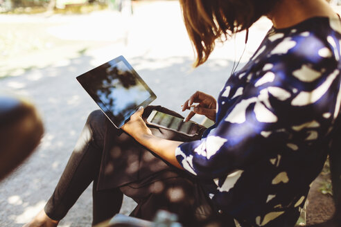 Side view of businesswoman using smart phone and digital tablet while sitting on bench - MASF02878