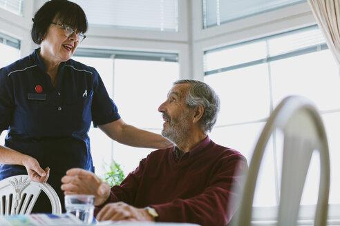 Senior man talking to female caretaker at home - MASF02884