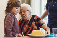 Senior woman talking to great grandson looking at sponge cake on table with caretaker standing at home - MASF02890