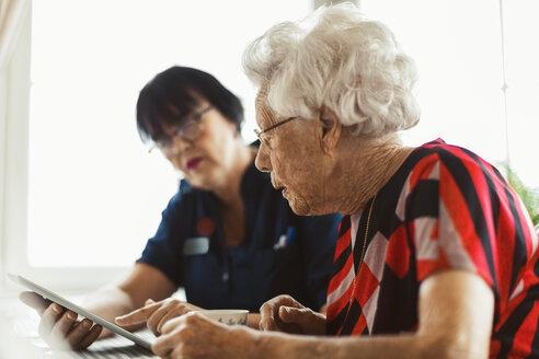 Senior woman using digital tablet with caretaker at home - MASF02893