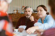 Senior man playing cards with family at home - MASF02896