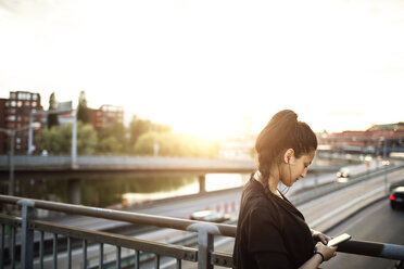 Side view of woman using mobile phone while on standing bridge against sky - MASF02899