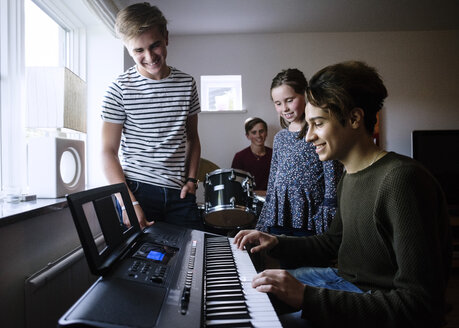 Siblings looking at young man playing piano keyboard in brightly lit room - MASF02905