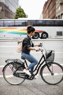 Side view of woman using mobile phone while riding bicycle on city street - MASF02908