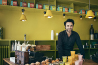 Portrait of smiling male owner standing in coffee shop - MASF02911