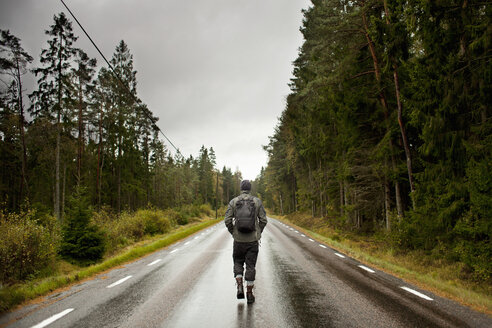 Rear view of hiker walking on country road amidst trees against sky - MASF02923