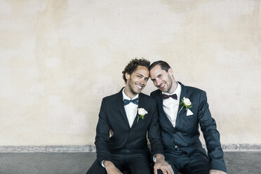 Portrait of newlywed gay couple sitting on bench against wall - MASF02926