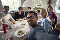 Portrait of smiling man taking selfie with family and friends at dinner party - MASF02938