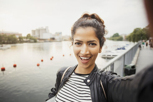 Portrait of smiling woman standing against river in city - MASF02941